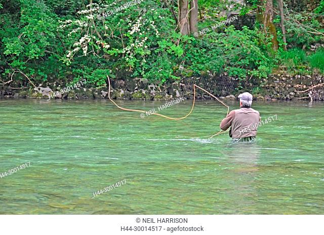 a fly-fisherman casts a fly across a swift river towards the far bank, while wading in deep water