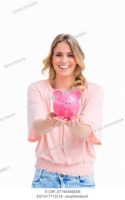 A smiling woman is holding a pink piggy bank in the palms of her hands against a white background