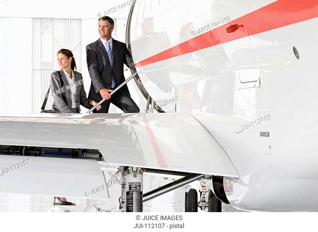 Smiling Businesswoman and Businessman boarding private jet