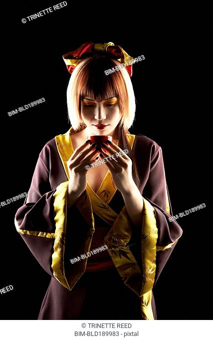 Asian woman in traditional clothing holding tea cup