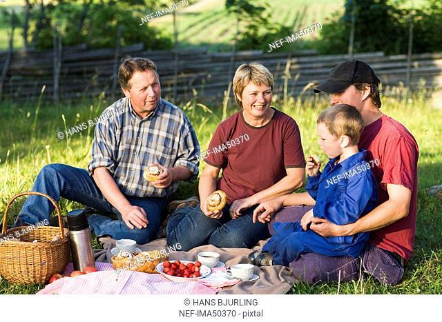 A farmer family taking a break in the grass, Sweden