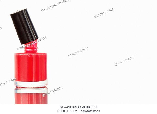 Close up of an opened nail polish flask against a white background