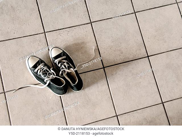 Pair of black sneakers on the tiles