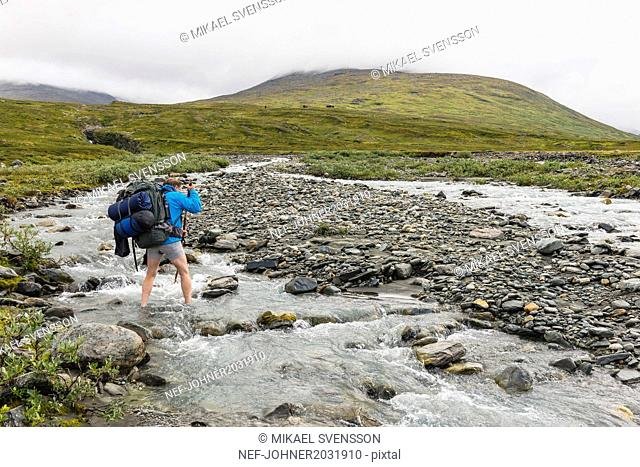 Hiker crossing river