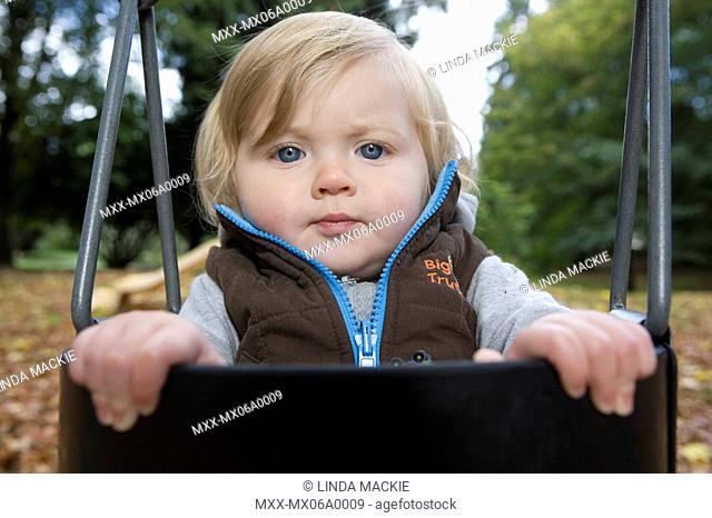 Close-up of blonde blue-eyed baby in a vest on s swing