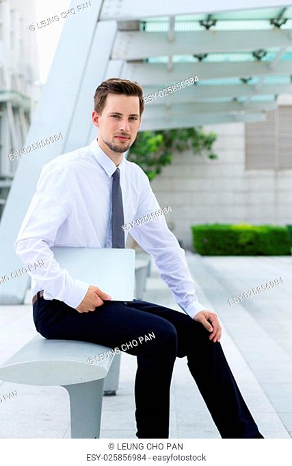 Caucasian young businessman hold with laptop computer at hong kong