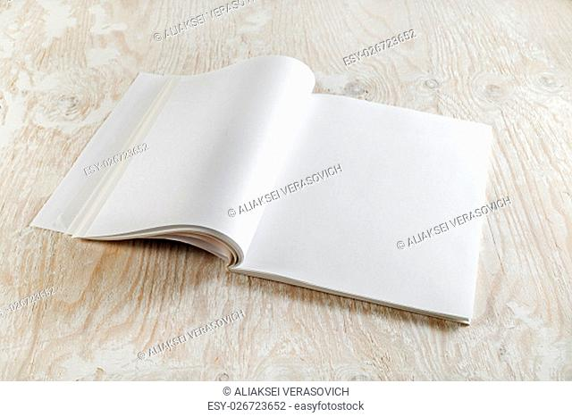 Blank opened brochure magazine on wooden background with soft shadows. Template for graphic designers portfolios