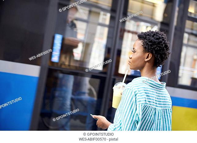 Woman with smoothie and smartphone waiting at bus stop