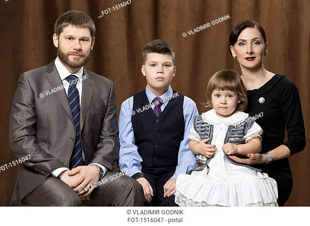 Portrait of family sitting against brown curtains in studio