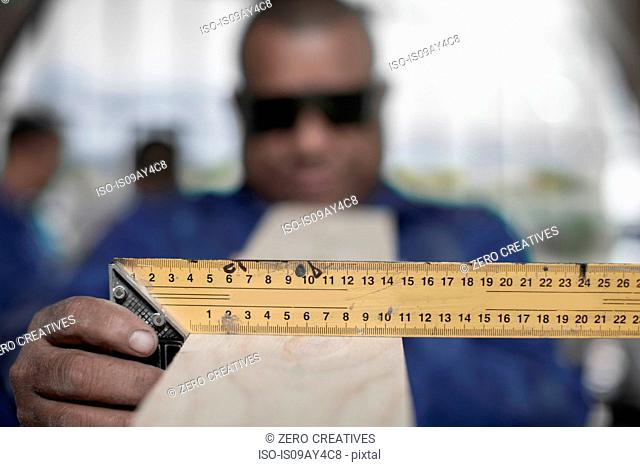 Close up of carpenter's hand measuring angle of plank in workshop