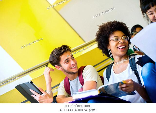 College students laughing while studying between classes