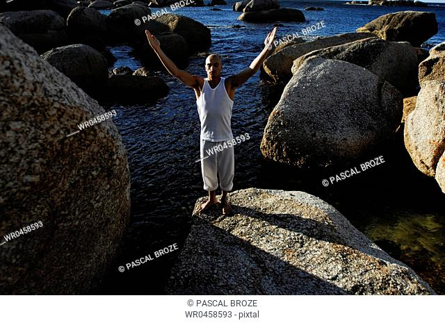 High angle view of a young man practicing yoga on a rock
