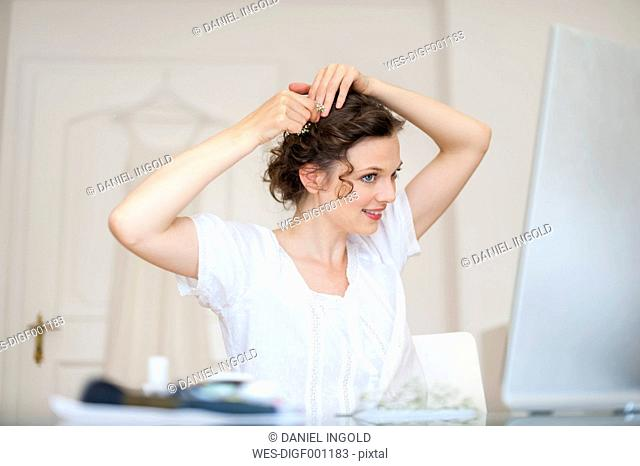 Woman at home putting flowers in her hair