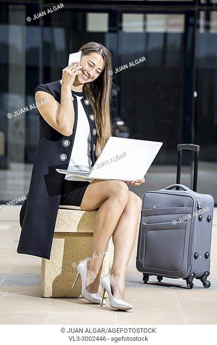 Young elegant businesswoman using laptop and talking smartphone while sitting at street with suitcase