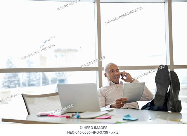 Businessman reviewing paperwork while on phone call at office desk