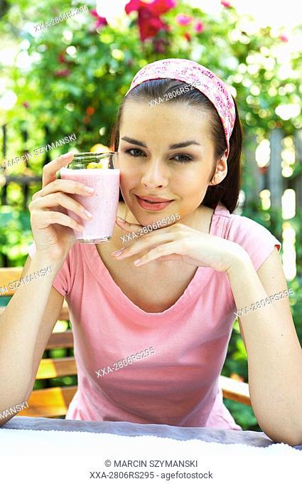 young woman drinking yoghurt in garden