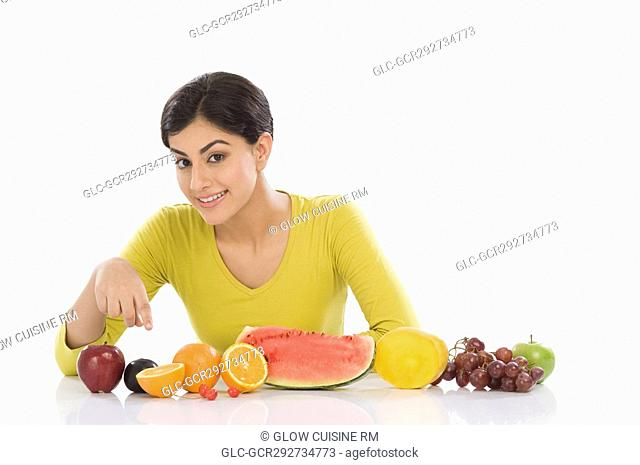 Portrait of a woman with a row of assorted fresh fruits