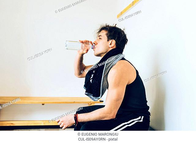 Man sitting in changing room drinking water from plastic bottle