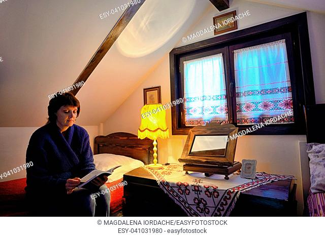 Female reading book on bed in traditional house