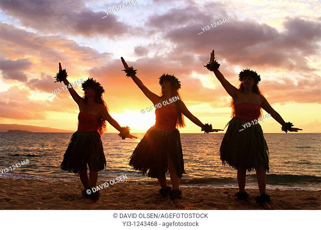 Three hula dancers at sunset at Palauea, Maui, Hawaii