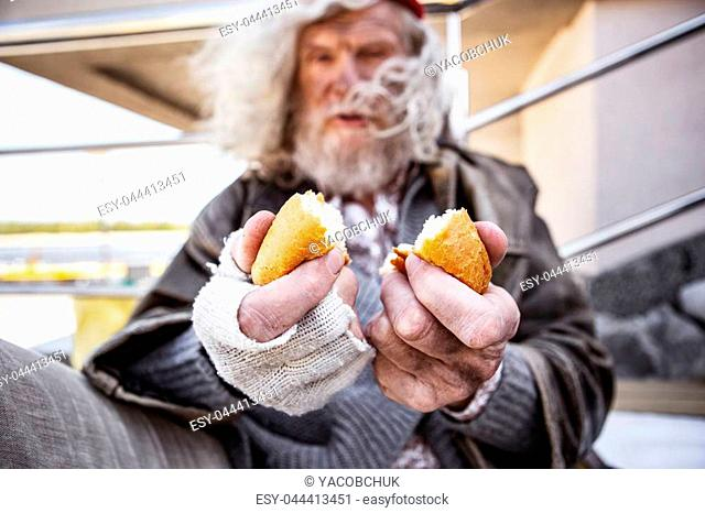 Piece of bread. Selective focus of delicious food being in hands of an aged homeless man