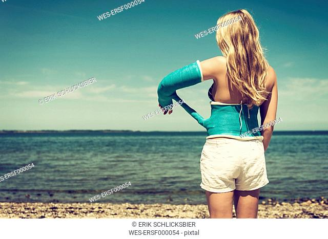 Young woman with plastered arm at beach