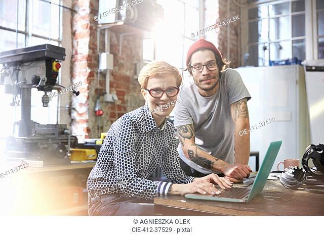 Portrait confident designers working at laptop in workshop