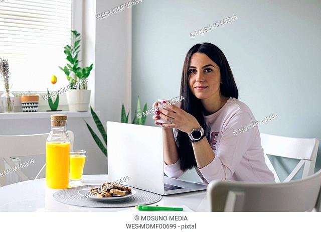 Beautiful young woman sitting at the table and drinking coffee at home