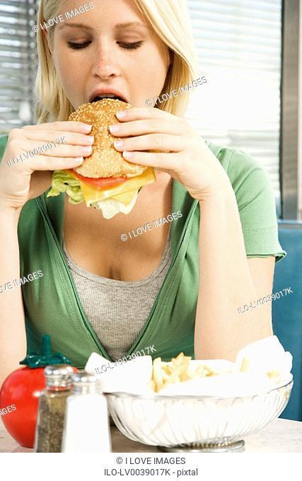 Teenage girl eating a hamburger in a diner