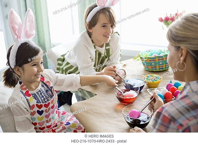 Children and mother coloring Easter eggs at table