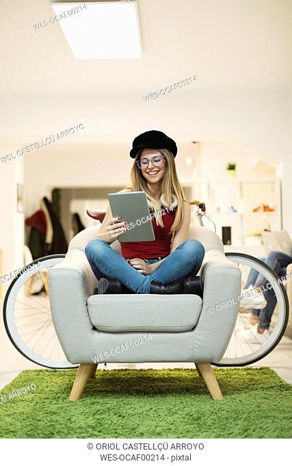 Casual young woman using tablet in coworking space