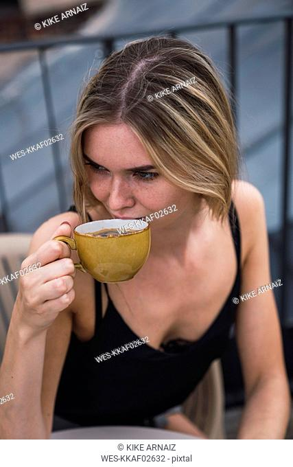 Young woman drinking cup of coffee on roof terrace