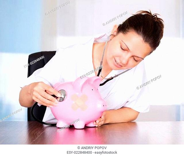 Doctor With Piggy Bank And Stethoscope