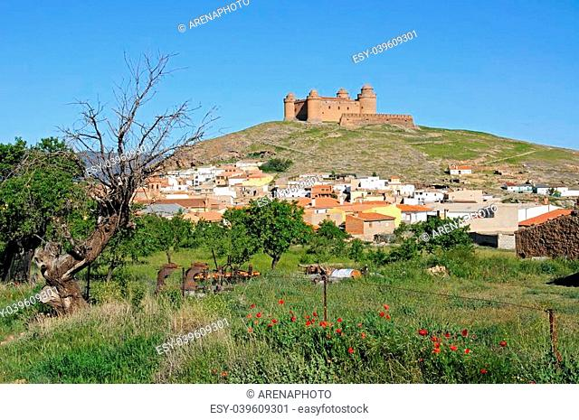 View of the castle (Castillo de La Calahorra) and town with poppies in the foreground, Lacalahorra, Granada Province, Andalucia, Spain