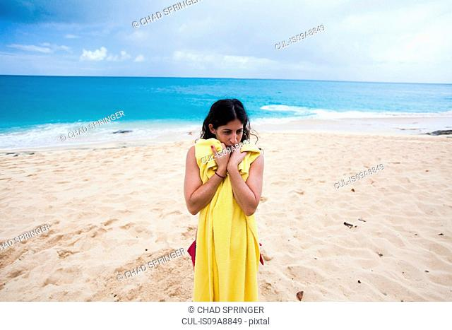 Woman holding yellow towel on beach, St Maarten, Netherlands