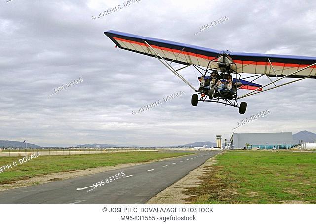 Ultralight aircraft flying in over runway, Camarillo, California, USA