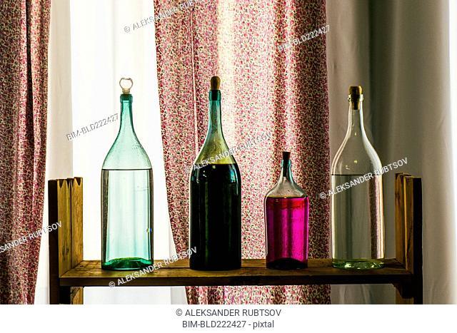 Bottles on shelf near window