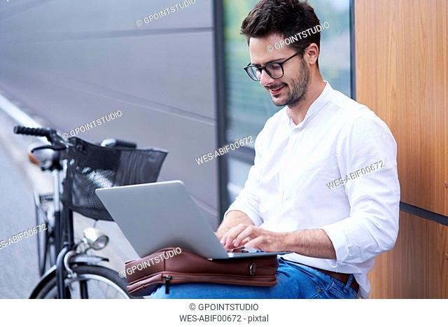 Businessman with bicycle using laptop outdoors