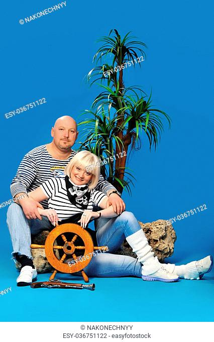 Photo of beautiful couples, men and women in the studio for the shooting in the image of pirates on a small palm tree background