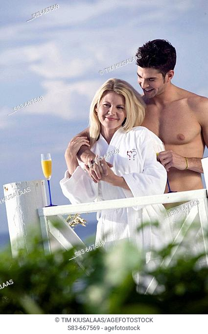Couple standing on deck in robes at beach