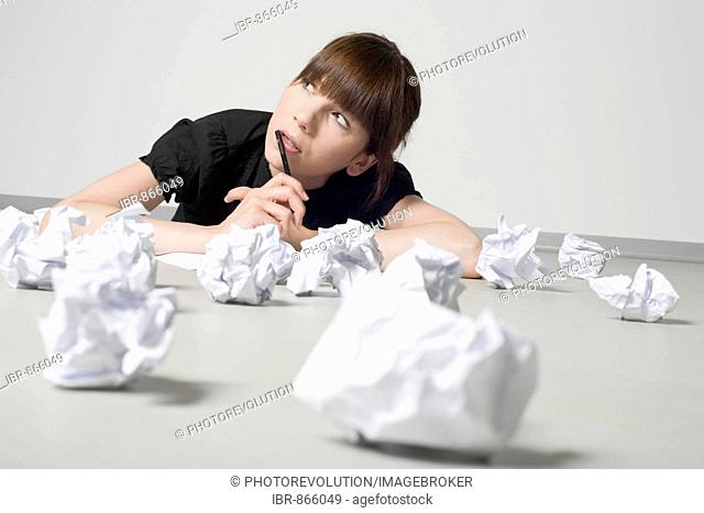 Young, dark-haired woman lying amongst screwed-up balls of paper, deliberating with a pen in her hand