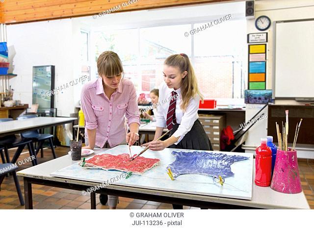 Art teacher guiding middle school student painting in art class