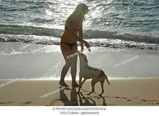 Unawatuna, Sri Lanka: woman playing with a dog at the beach