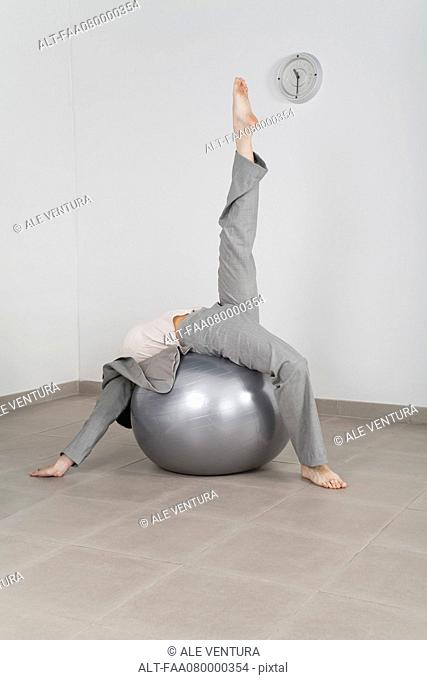 Businesswoman stretching on fitness ball in office