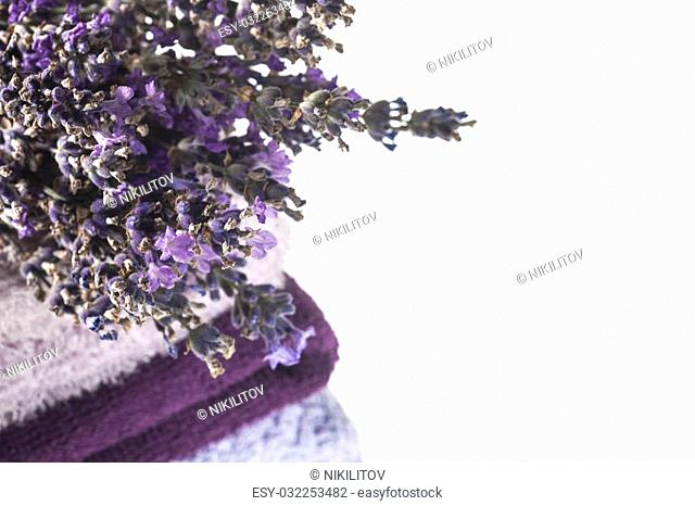 Spa background with bunch of lavender and towels on a white background with copy space