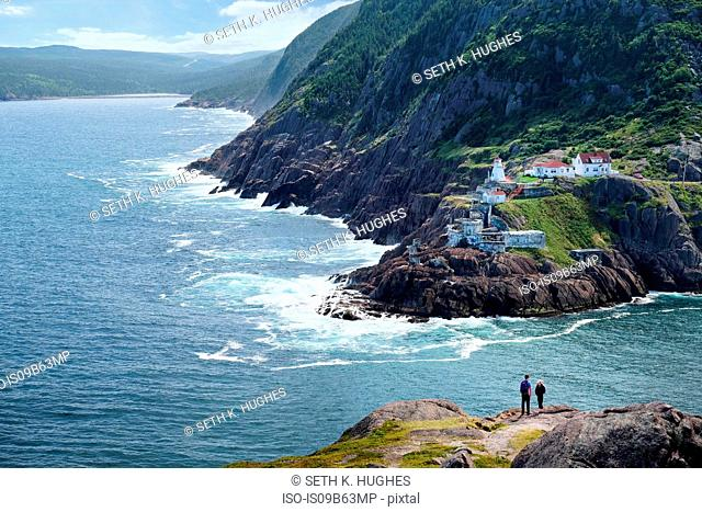 Couple looking out from coastal cliff, St John's, Newfoundland, Canada