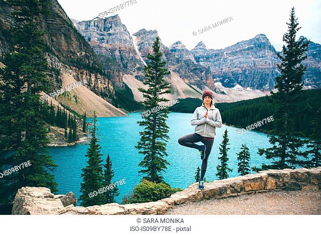 Woman practising yoga, Moraine Lake, Banff, Canada