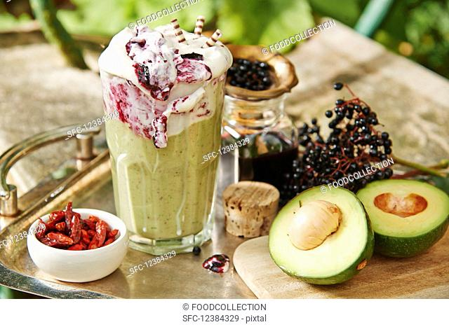 A smoothie with avocado, chili and elderberry frosting on a garden table
