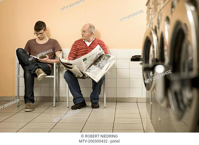 Men reading book and newspaper in laundry