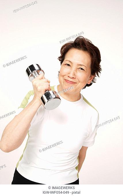 Senior woman holding dumbbell, portrait